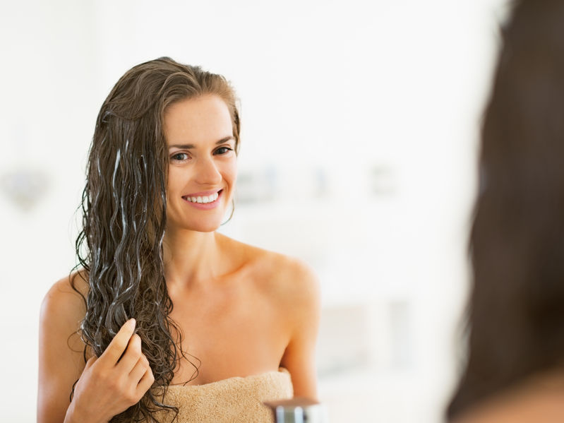 25078494 - happy young woman applying hair mask in bathroom
